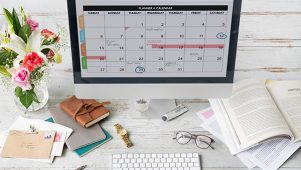 Work calendar on iMac computer placed on white work desk