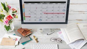 Work calendar on iMac computer placed on white work desk
