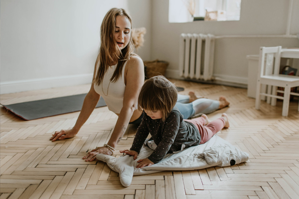 Personal training from home - Mother and daughter exercising together at home.