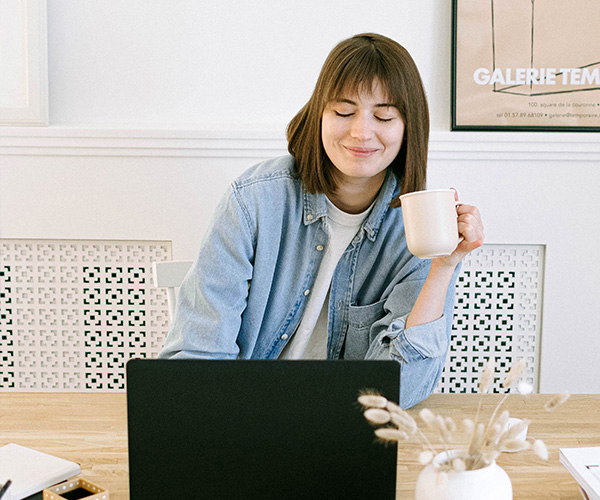 Lady smiling as she drinks a cup of tea and works from laptop