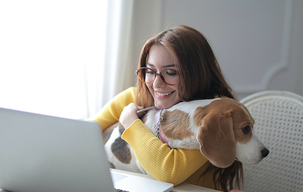 Lady working from home, hugging her dog as it sits on her lap.