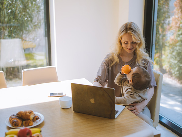 Mother working from home, with young baby sat on her knee and contently playing with an orange.