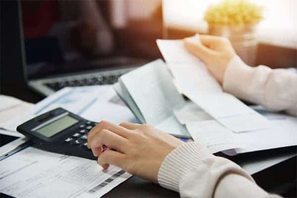 Freelancer looking through her invoices to work out her expenses, using a calculator.