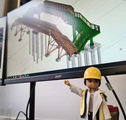 A female engineer barbie known as a 'Lottie Doll' in front of a computer screen