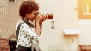 a freelance photographer taking a photo of a cityscape on her camera