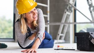 construction worker sitting on the ground holding arm following an injury